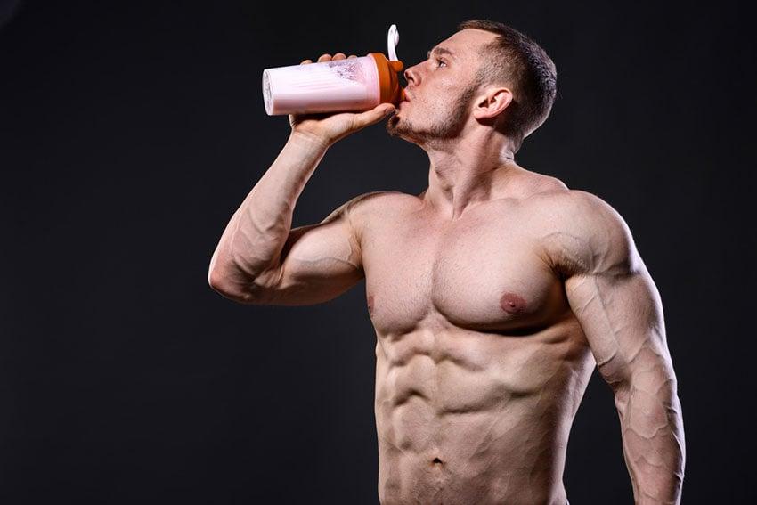 umięśniony mężczyzna pije szejka proteinowego
