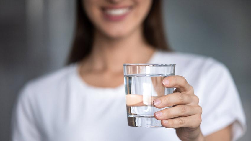 kobieta pije wodę na kaca